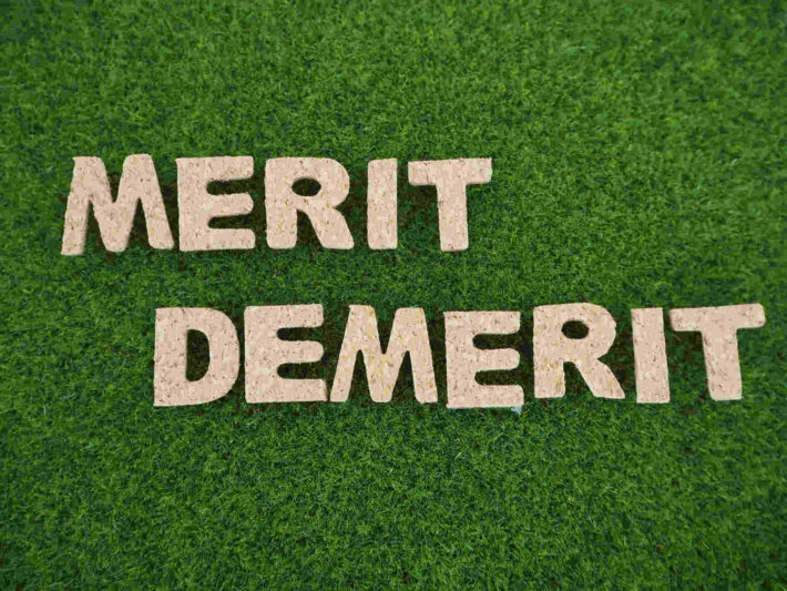 芝生の上に置かれたメリット、デメリットの文字