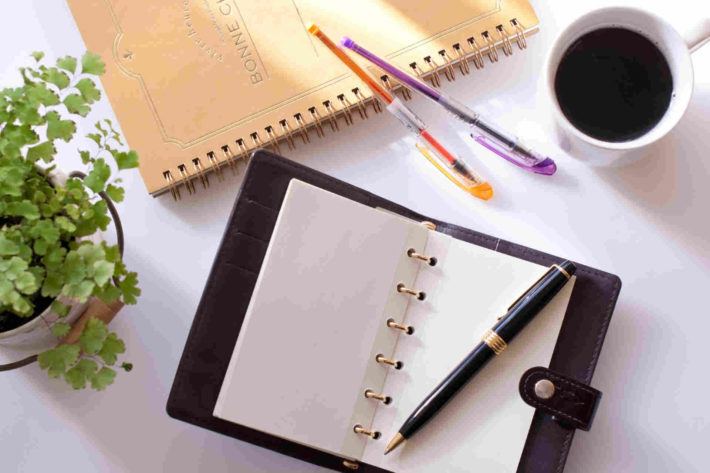 机の上に置かれた手帳とペン