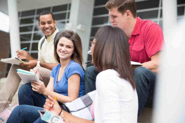 大学の学内で集まり話している男女