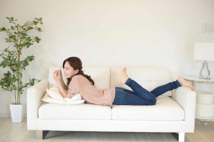 ソファーでゴロゴロ横になっている女性