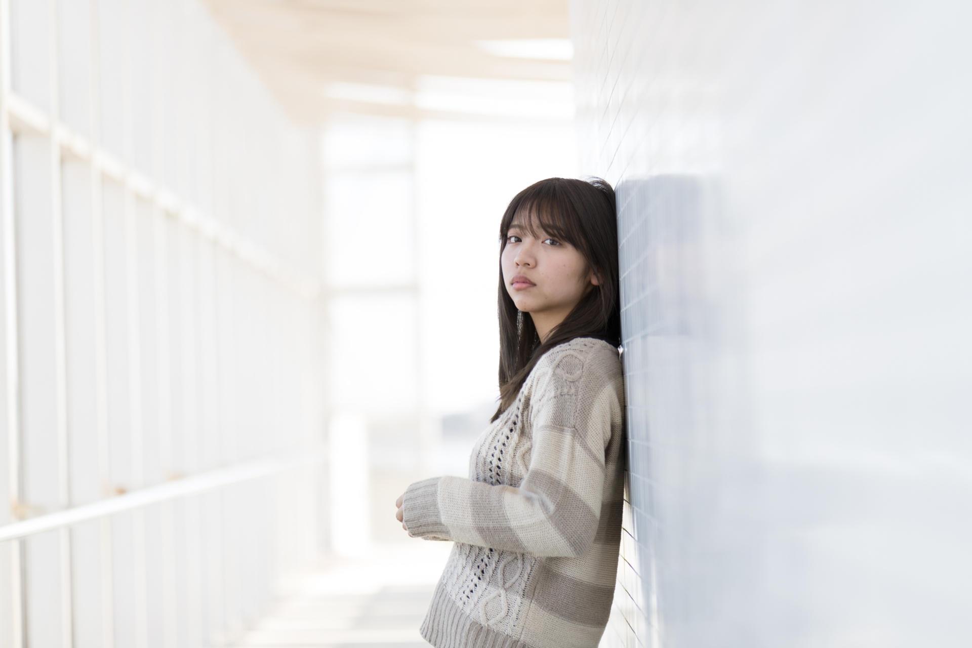壁に寄りかかっている大学生の女の子
