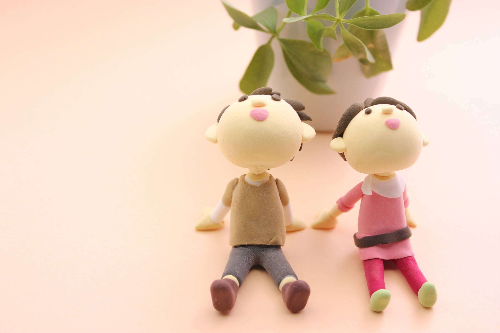 手をつないで座っているカップル人形