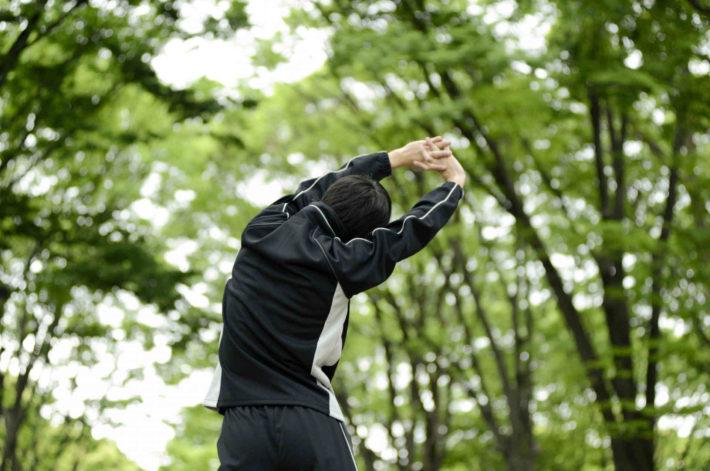 森の中でストレッチしている男性の後ろ姿