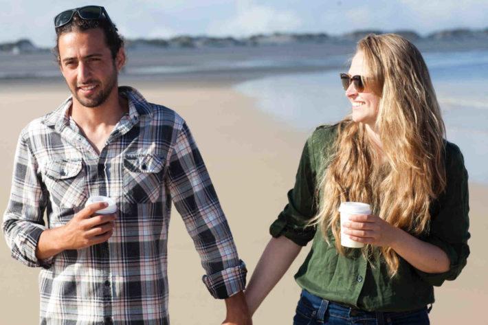 海辺を手をつないで歩くカップル