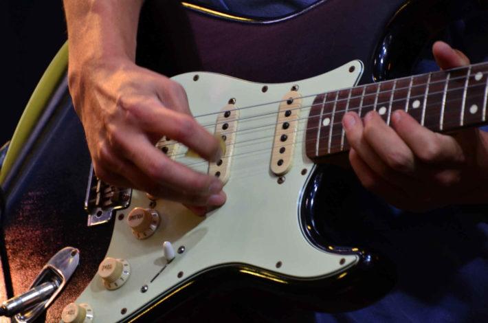 フェンダーのギターを弾いている男性の手元