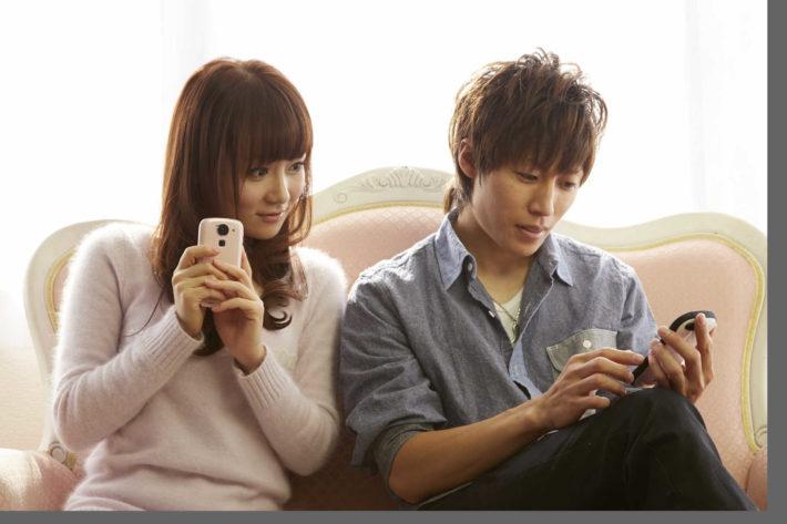 ソファーに座り携帯で遊ぶカップル