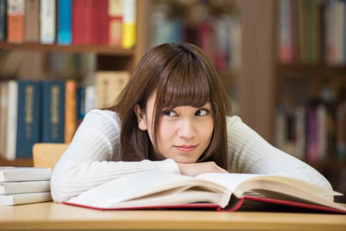 本の上で頬杖をつく女性