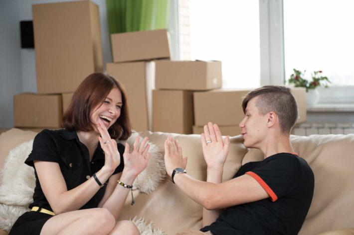 ソファーに座り笑い合っているカップル