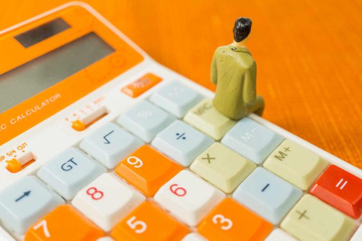 電卓の上に腰掛けている男性の人形の背中