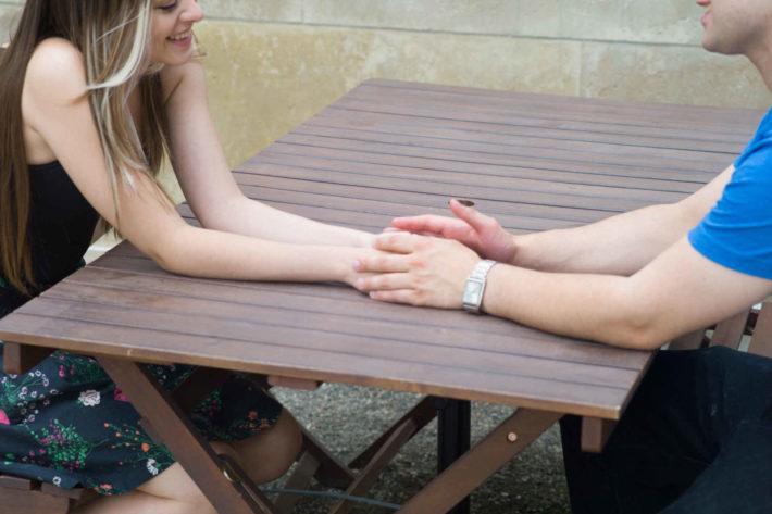 テーブルの上で手を触れ合っている男女のカップル