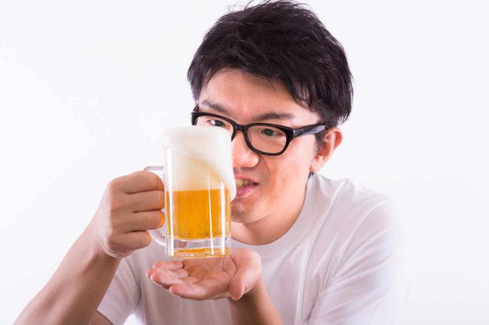 ビールを飲もうとしているメガネのオタク男性