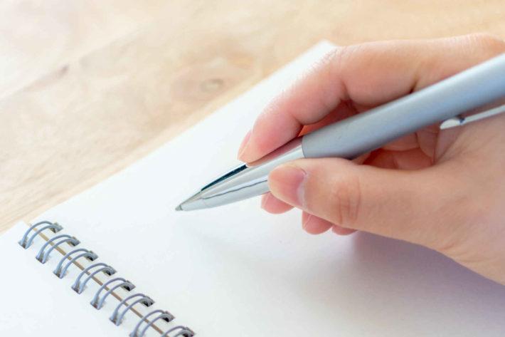 字を書く女性の手元