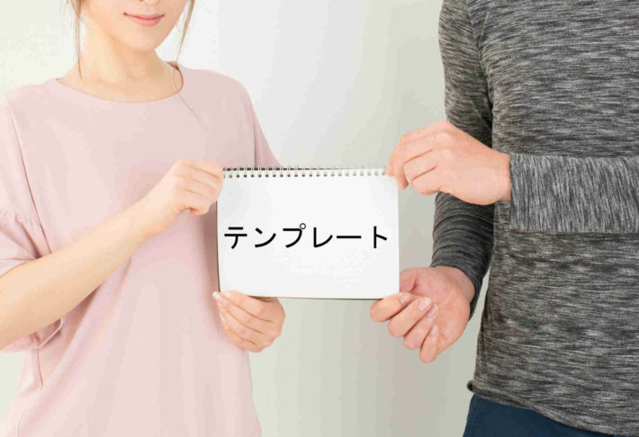 テンプレートと書かれた画用紙を持ち合うカップル