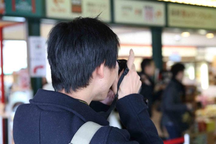 人並みを撮影しているオタク男性、後ろ姿