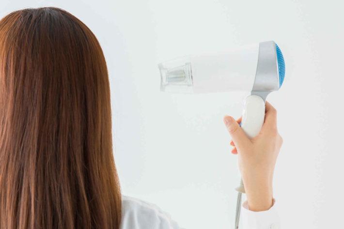 ヘアドライヤーで髪の毛を乾かしている女性