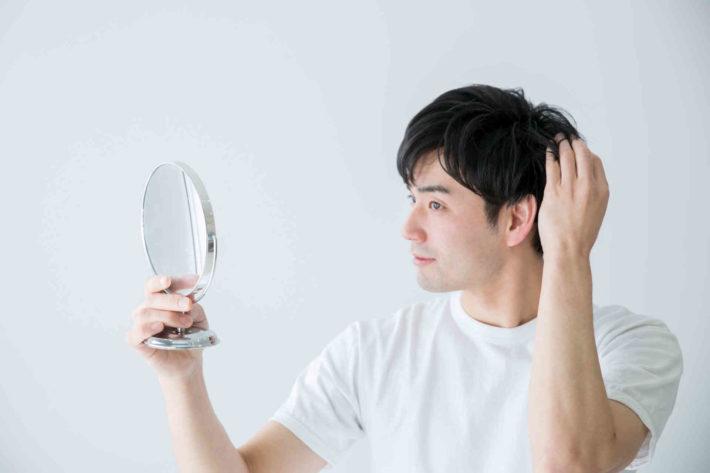 手鏡で髪型をチェックしている男性