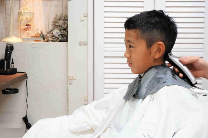 髪を家族に切ってもらっている男の子