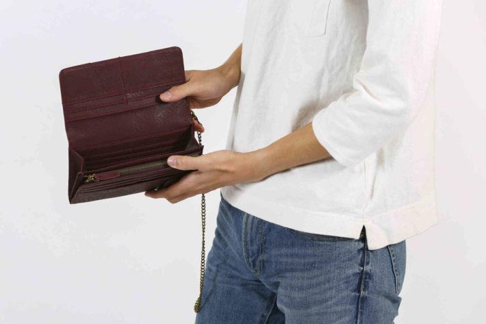 すっからかんの財布を見せている男性
