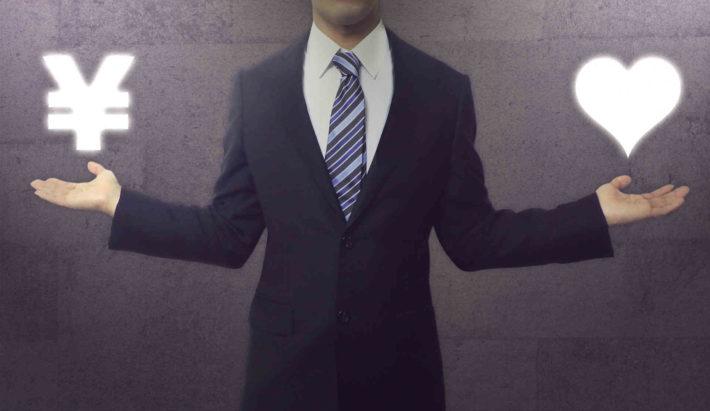 スーツの男性が両手にお金とハートを釣り合わせている画像
