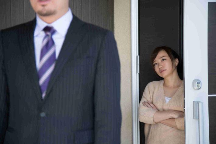 玄関先で夫を仕事に送り出している、しかめっ面の妻