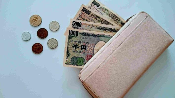 女性物のラウンドジップ長財布からお札とコインが出ている画像