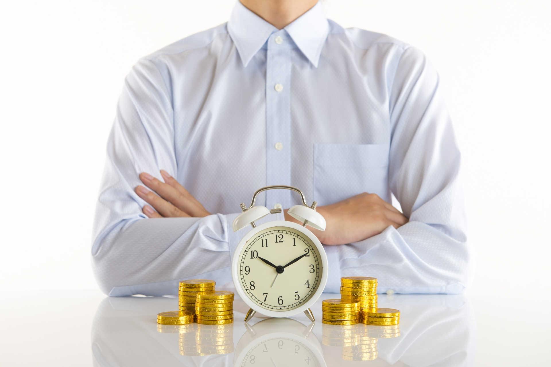 腕を組む男性とテーブルの上にある時計とコイン