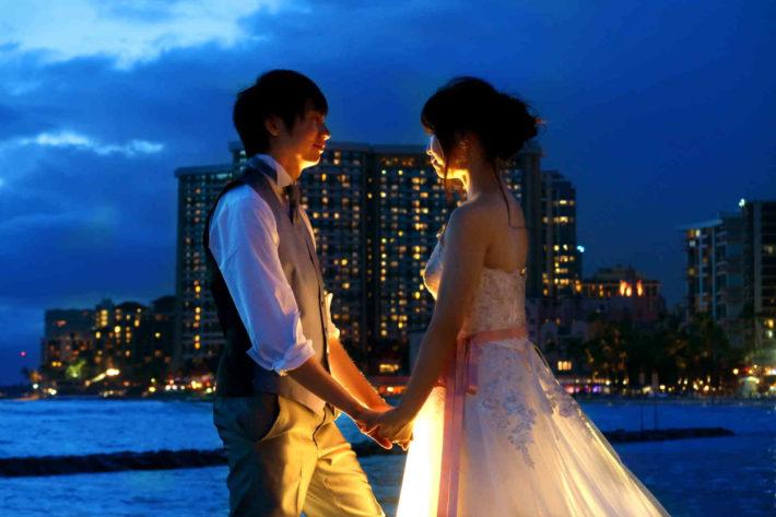 夜の海辺で結婚式を挙げ見つめ合っている男女