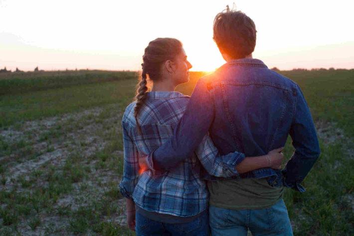 夕日を見つめる男女のカップル