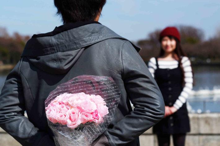花束を背中に隠し、女性に渡そうとしている男性
