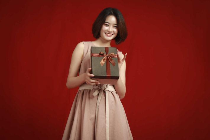 プレゼントボックスを見せびらかす笑顔の女性