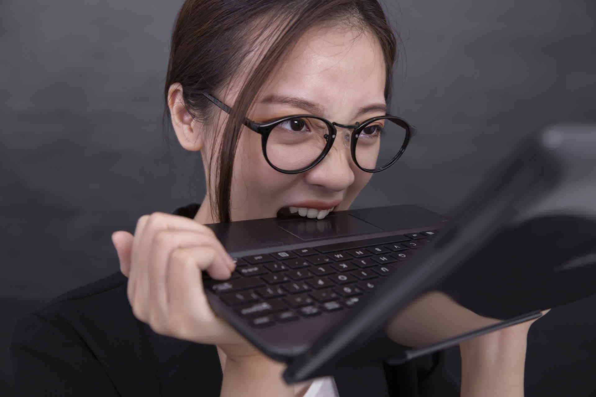 キーボードを噛んでいる女性