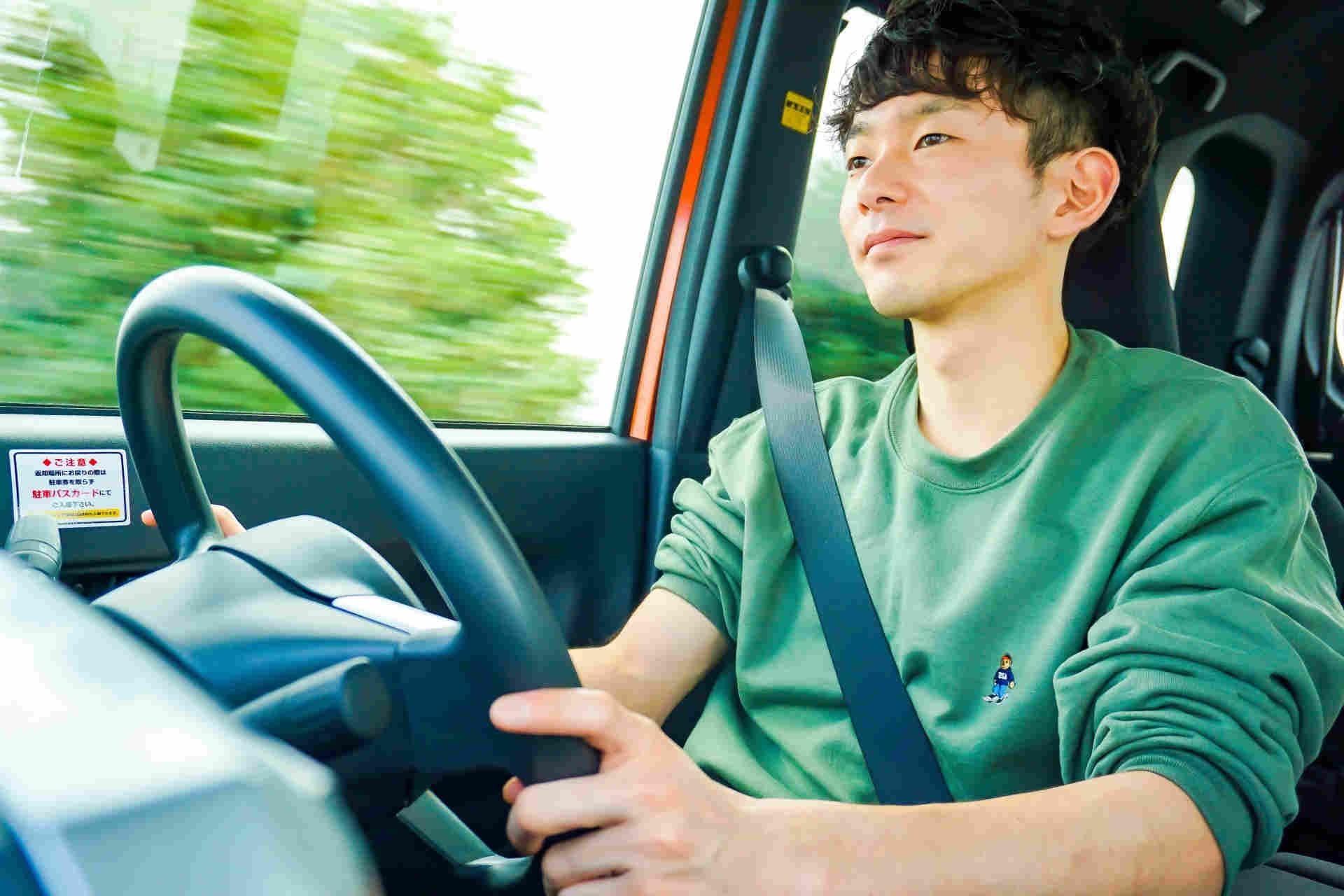 車を運転する緑のセーターを着た平凡そうな男性