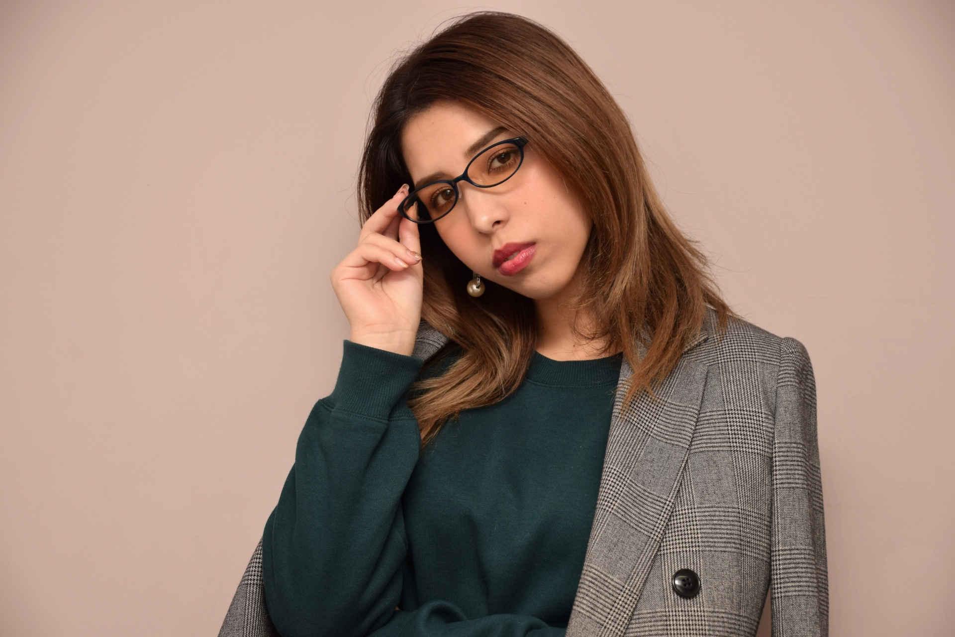 メガネの縁を持ってかけ直している女性