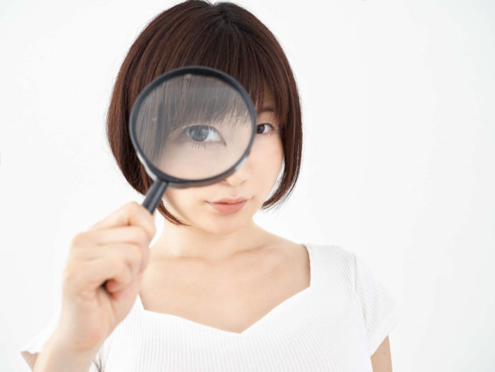 虫眼鏡を覗く女性