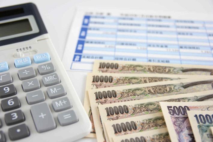 年収計算で机に置かれた電卓と源泉徴収