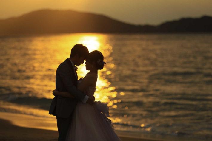夕暮れ時の砂浜で抱きしめ合うタキシードとウエディングドレスの女性