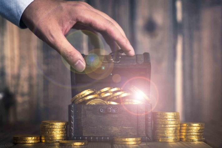 お金が入っている宝箱を開ける男性の手