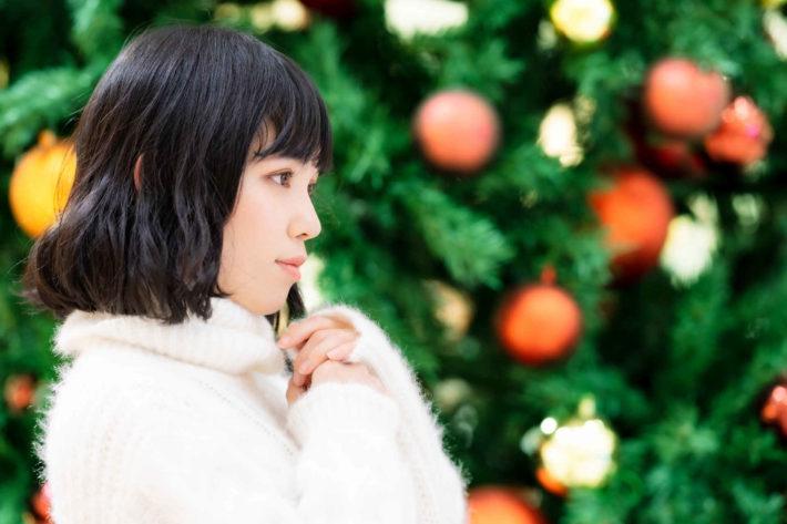 クリスマスツリーの前で誰かを待っている女性