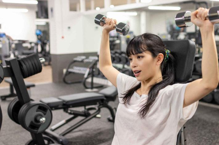 フィットネスジムでトレーニングしている美人女性