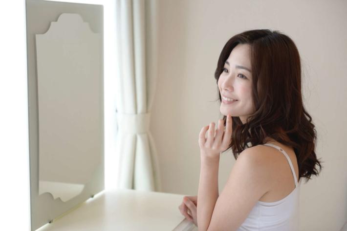鏡を見て微笑んでいる女性
