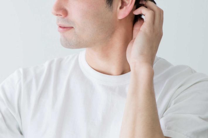 鏡を見て髪を気にしている男性