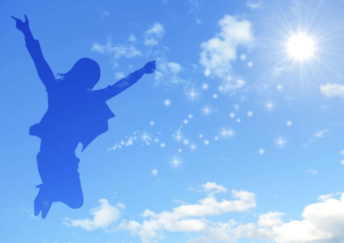 空に映った、ジャンプしている女性のシルエット