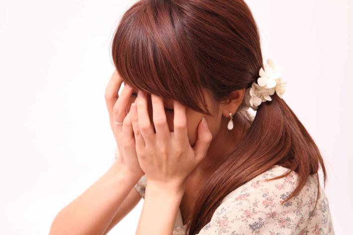 顔を隠して俯く女性