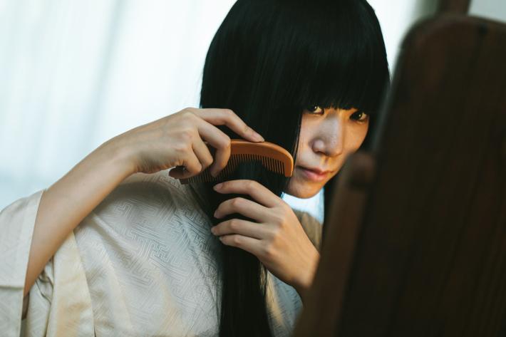 長い黒髪を解く暗い表情をした女性