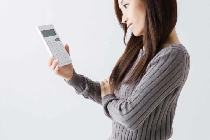 電卓を片手に悩んでいる女性