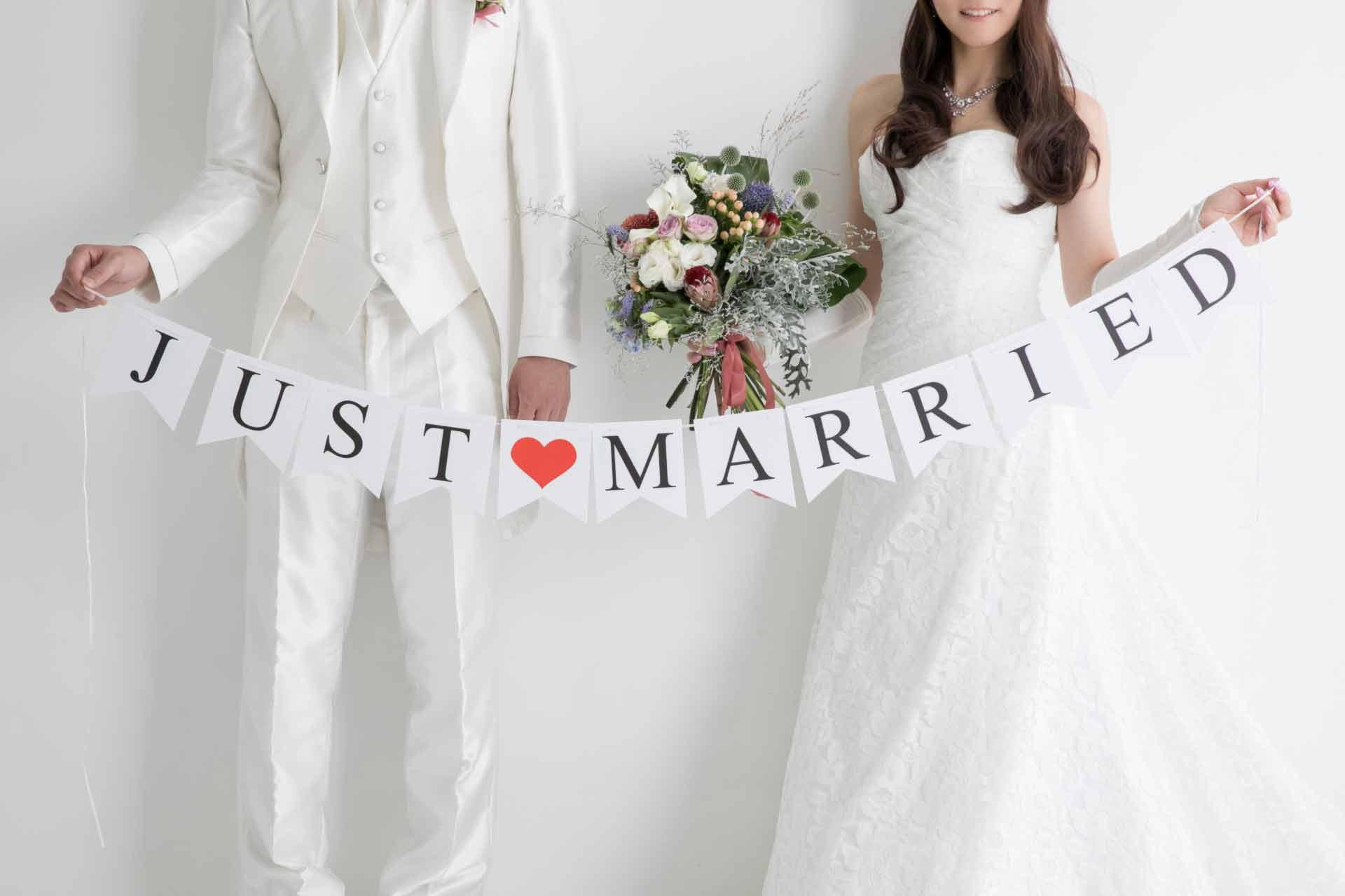 「JUST MARRIED」のオーナメントを持つ正装した男女のカップル