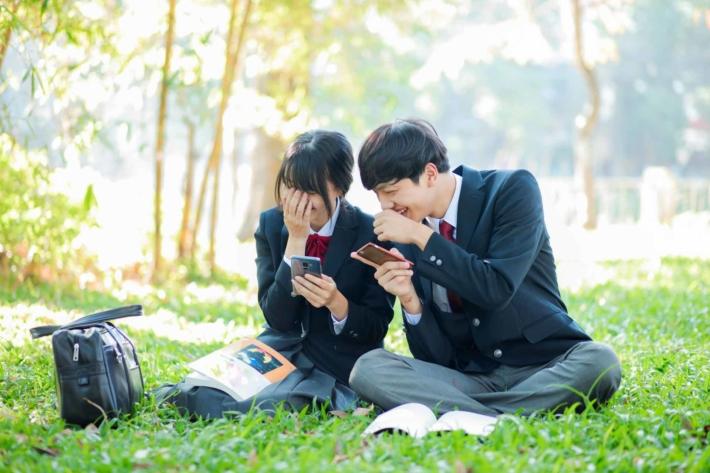 芝生の上に座り仲良く話している高校生の男女