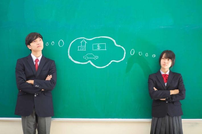 黒板の前に立って考えている男子と女子