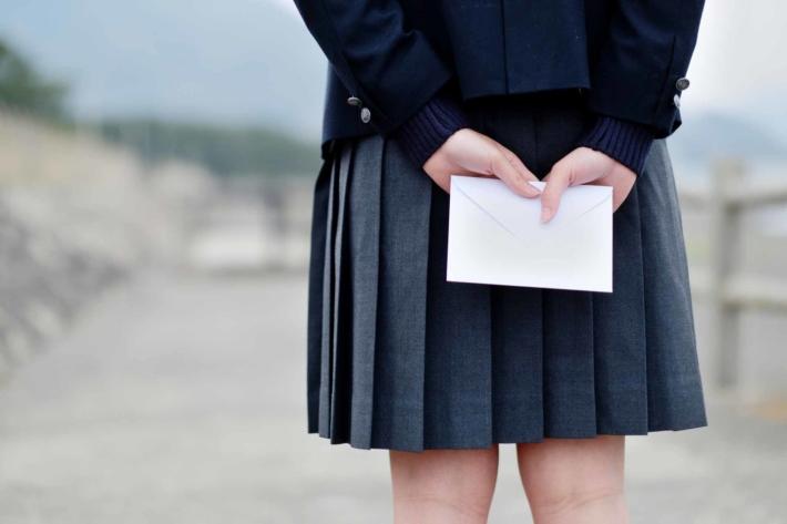 後ろ手にラブレターを隠し持って誰かを待っている女子高生