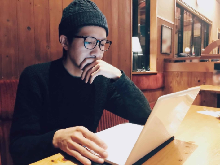 カフェでMacbookを操作しているニット帽でメガネの男性
